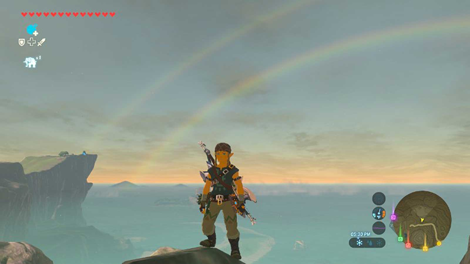 Link on the mountainside with a double rainbow apparent in the background